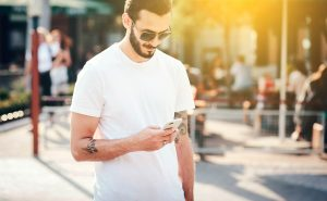young man with tattoos looking down at mobile phone