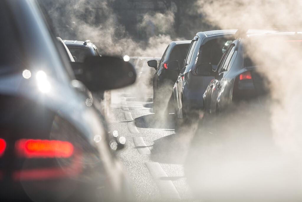Cars in traffic jam emitting exhaust fumes